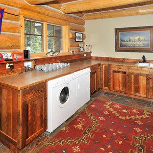 Immagine di una grande lavanderia multiuso stile rurale con lavello a doppia vasca, ante in stile shaker, top in laminato, pavimento in ardesia, lavatrice e asciugatrice affiancate, ante in legno bruno e pareti grigie