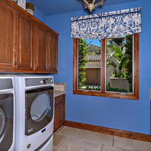 Immagine di una sala lavanderia stile marinaro di medie dimensioni con lavello da incasso, ante con bugna sagomata, ante marroni, top piastrellato, pareti blu, pavimento in travertino, lavatrice e asciugatrice affiancate, pavimento beige e top beige