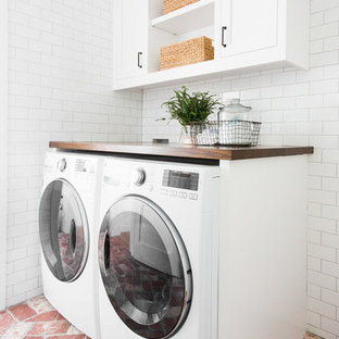 This is an example of a mid-sized beach style dedicated laundry room in Salt Lake City with white cabinets, wood benchtops, white walls, brick floors, a side-by-side washer and dryer, red floor and brown benchtop.