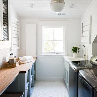 Idéer för en stor maritim beige tvättstuga enbart för tvätt, med blå skåp, träbänkskiva, vita väggar, en tvättmaskin och torktumlare bredvid varandra och vitt golv