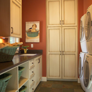 This is an example of a large traditional galley separated utility room in Grand Rapids with a submerged sink, recessed-panel cabinets, quartz worktops, orange walls, slate flooring, a stacked washer and dryer and light wood cabinets.
