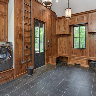 Photo of a large traditional u-shaped utility room in Other with shaker cabinets, medium wood cabinets, a side by side washer and dryer, grey floors, brown walls and porcelain flooring.
