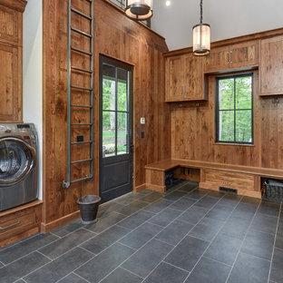 Klassisk inredning av ett stort u-format grovkök, med skåp i shakerstil, skåp i mellenmörkt trä, en tvättmaskin och torktumlare bredvid varandra, grått golv, bruna väggar och klinkergolv i porslin