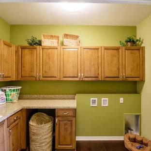 Foto di una sala lavanderia classica di medie dimensioni con lavello da incasso, ante in stile shaker, ante in legno chiaro, top in laminato, pareti verdi, pavimento in legno massello medio, lavatrice e asciugatrice affiancate e pavimento marrone