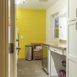 Immagine di una lavanderia multiuso tradizionale di medie dimensioni con lavatoio, ante con riquadro incassato, ante bianche, top in granito, pareti gialle, moquette, lavatrice e asciugatrice affiancate e pavimento marrone