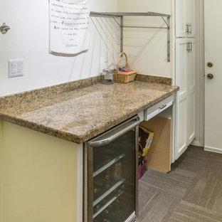 Esempio di una lavanderia multiuso tradizionale di medie dimensioni con lavatoio, ante con riquadro incassato, ante bianche, top in granito, pareti gialle, moquette, lavatrice e asciugatrice affiancate e pavimento marrone