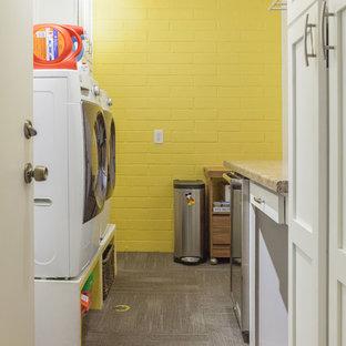 Idee per una lavanderia multiuso tradizionale di medie dimensioni con lavatoio, ante con riquadro incassato, ante bianche, top in granito, pareti gialle, moquette, lavatrice e asciugatrice affiancate e pavimento marrone