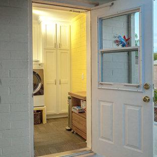 Foto di una lavanderia multiuso chic di medie dimensioni con lavatoio, ante con riquadro incassato, ante bianche, top in granito, pareti gialle, moquette, lavatrice e asciugatrice affiancate e pavimento marrone