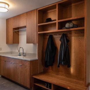 Immagine di una lavanderia multiuso minimal di medie dimensioni con lavello sottopiano, ante lisce, ante marroni, top in superficie solida, pareti bianche, pavimento in gres porcellanato, lavatrice e asciugatrice affiancate, pavimento grigio e top grigio
