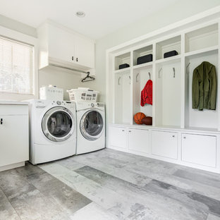 This is an example of a large contemporary galley utility room in New York with a built-in sink, open cabinets, white cabinets, white walls, porcelain flooring and a side by side washer and dryer.