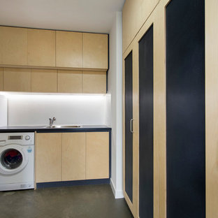Large contemporary utility room in Melbourne with a built-in sink, flat-panel cabinets, light wood cabinets, white walls, concrete flooring, grey floors and blue worktops.