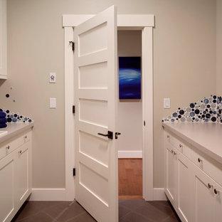 Idéer för att renovera en mellanstor funkis parallell tvättstuga, med en nedsänkt diskho, skåp i shakerstil, vita skåp, laminatbänkskiva, beige väggar, klinkergolv i keramik och en tvättmaskin och torktumlare bredvid varandra