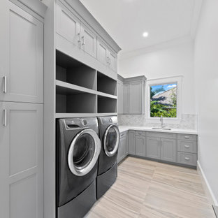 Design ideas for a large traditional l-shaped separated utility room in Miami with a submerged sink, shaker cabinets, grey cabinets, quartz worktops, white walls, porcelain flooring, a side by side washer and dryer, beige floors and white worktops.