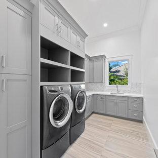 Inredning av en klassisk stor vita l-formad vitt tvättstuga enbart för tvätt, med en undermonterad diskho, skåp i shakerstil, grå skåp, bänkskiva i kvartsit, vita väggar, klinkergolv i porslin, en tvättmaskin och torktumlare bredvid varandra och beiget golv