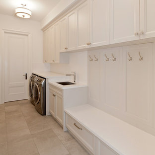 Mid-sized contemporary single-wall utility room in Los Angeles with an undermount sink, shaker cabinets, white cabinets, quartz benchtops, white walls, limestone floors and a side-by-side washer and dryer.