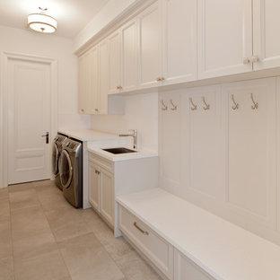 Ispirazione per una lavanderia multiuso minimal di medie dimensioni con lavello sottopiano, ante in stile shaker, ante bianche, top in quarzo composito, pareti bianche, pavimento in pietra calcarea e lavatrice e asciugatrice affiancate