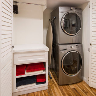 Inspiration for a mid-sized transitional single-wall medium tone wood floor and brown floor laundry closet remodel in Los Angeles with shaker cabinets, white cabinets, white walls and a stacked washer/dryer