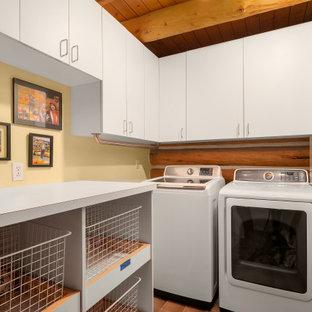 Foto di una sala lavanderia stile rurale di medie dimensioni con ante lisce, ante bianche, pareti gialle, pavimento in gres porcellanato, lavatrice e asciugatrice affiancate, pavimento marrone, soffitto in legno e pareti in legno