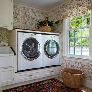 Modelo de cuarto de lavado papel pintado, clásico, grande, papel pintado, con pila para lavar, armarios con rebordes decorativos, puertas de armario beige, encimera de madera, lavadora y secadora juntas, encimeras marrones y papel pintado