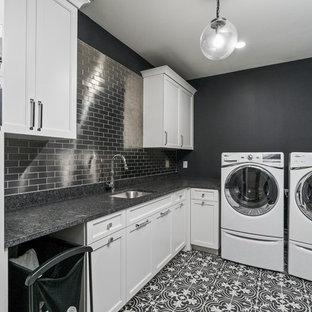 Bild på en vintage svarta l-formad svart tvättstuga enbart för tvätt, med en undermonterad diskho, luckor med profilerade fronter, vita skåp, svarta väggar, en tvättmaskin och torktumlare bredvid varandra och svart golv