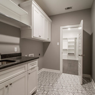 Large modern single-wall separated utility room in Little Rock with a submerged sink, shaker cabinets, white cabinets, engineered stone countertops, grey walls, ceramic flooring, a side by side washer and dryer, multi-coloured floors and black worktops.