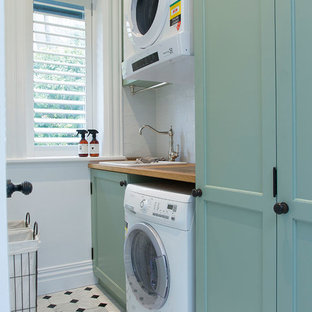 Photo of a large country single-wall utility room in Sydney with recessed-panel cabinets, white walls, a drop-in sink, wood benchtops, marble floors, a stacked washer and dryer, turquoise cabinets and beige benchtop.