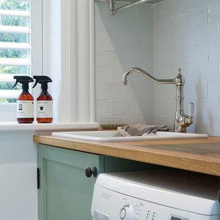 Inredning av ett lantligt stort linjärt grovkök, med luckor med infälld panel, vita väggar, en nedsänkt diskho, träbänkskiva, marmorgolv, en tvättpelare och turkosa skåp