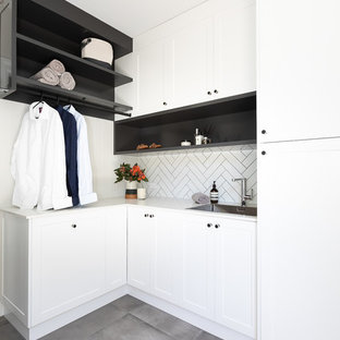 Design ideas for a mid-sized contemporary l-shaped utility room in Brisbane with a drop-in sink, shaker cabinets, white cabinets, quartz benchtops, white walls, ceramic floors, a concealed washer and dryer, grey floor and white benchtop.