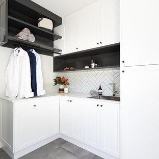 Foto på ett mellanstort funkis vit l-format grovkök, med en nedsänkt diskho, skåp i shakerstil, vita skåp, bänkskiva i kvarts, vita väggar, klinkergolv i keramik, tvättmaskin och torktumlare byggt in i ett skåp och grått golv