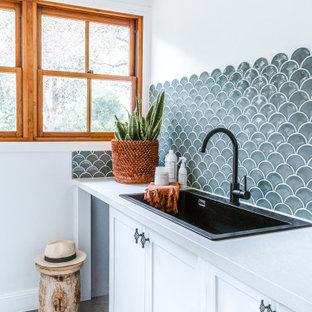 Inspiration för en maritim vita vitt tvättstuga, med en dubbel diskho, luckor med infälld panel, vita skåp, blått stänkskydd, stänkskydd i keramik, vita väggar och grått golv