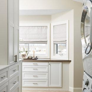 Idee per una sala lavanderia tradizionale di medie dimensioni con ante in stile shaker, ante bianche, pareti beige, moquette, lavatrice e asciugatrice a colonna, pavimento marrone e top marrone