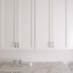 Idee per una piccola sala lavanderia stile americano con ante in stile shaker, ante grigie, top in granito, pareti bianche, pavimento in gres porcellanato e lavatrice e asciugatrice affiancate