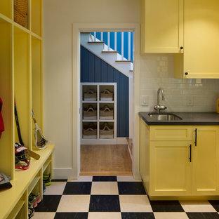 Foto di una grande lavanderia multiuso american style con ante gialle, pareti bianche, lavello sottopiano, ante con riquadro incassato, top in saponaria, pavimento con piastrelle in ceramica e pavimento multicolore