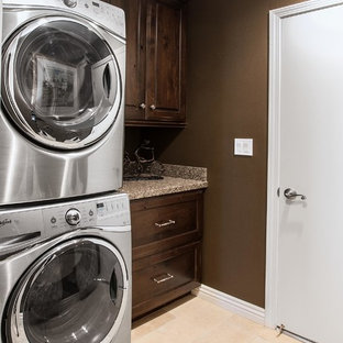 Small elegant single-wall porcelain tile dedicated laundry room photo in Orange County with an undermount sink, recessed-panel cabinets, dark wood cabinets, granite countertops, brown walls and a stacked washer/dryer