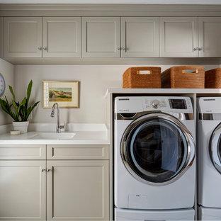 Exempel på en stor klassisk vita l-formad vitt tvättstuga enbart för tvätt, med en undermonterad diskho, luckor med infälld panel, grå skåp, bänkskiva i kvarts, beige väggar, klinkergolv i porslin, en tvättmaskin och torktumlare bredvid varandra och beiget golv