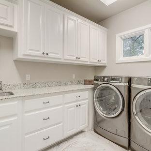 Ispirazione per una sala lavanderia country di medie dimensioni con lavello sottopiano, ante con bugna sagomata, ante bianche, top in quarzo composito, pareti grigie, pavimento con piastrelle in ceramica, lavatrice e asciugatrice affiancate e pavimento grigio