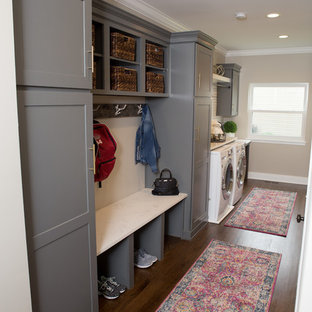Example of a mid-sized transitional u-shaped medium tone wood floor and brown floor utility room design in Chicago with a farmhouse sink, shaker cabinets, quartz countertops, white backsplash, subway tile backsplash, white countertops, gray cabinets, beige walls and a side-by-side washer/dryer