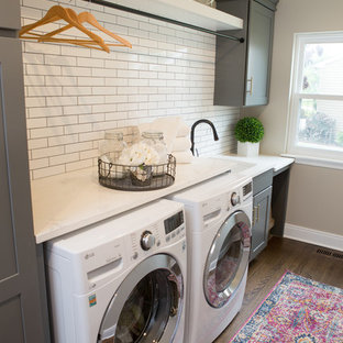 Photo of a mid-sized transitional u-shaped utility room in Chicago with a farmhouse sink, shaker cabinets, quartz benchtops, white splashback, subway tile splashback, medium hardwood floors, brown floor, white benchtop, grey cabinets, beige walls and a side-by-side washer and dryer.