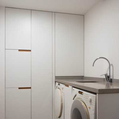 Mid-sized minimalist single-wall gray floor dedicated laundry room photo in Valencia with an undermount sink, white cabinets and white walls