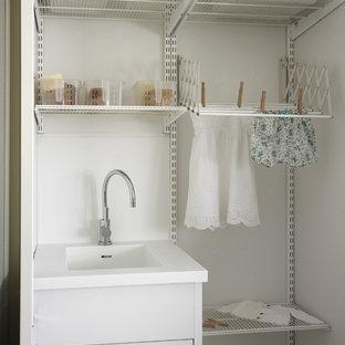 Cette photo montre une petit buanderie linéaire tendance dédiée avec des portes de placard blanches, un mur blanc, un sol en bois clair, des machines côte à côte et un évier intégré.