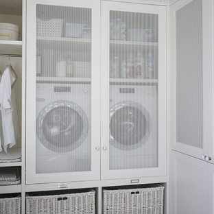 Example of a mid-sized danish single-wall laundry closet design in Barcelona with white cabinets and a side-by-side washer/dryer