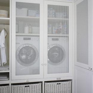 Inspiration för en mellanstor nordisk linjär liten tvättstuga, med vita skåp och en tvättmaskin och torktumlare bredvid varandra
