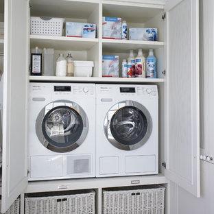 Modelo de armario lavadero lineal, escandinavo, de tamaño medio, con puertas de armario blancas y lavadora y secadora juntas