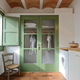Diseño de cuarto de lavado lineal, mediterráneo, de tamaño medio, con armarios con paneles lisos, puertas de armario blancas, encimera de madera, suelo de madera oscura, suelo marrón y paredes blancas