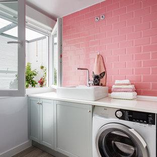 Immagine di una sala lavanderia contemporanea di medie dimensioni con lavello a vasca singola, ante grigie, pareti bianche, pavimento con piastrelle in ceramica, lavatrice e asciugatrice affiancate, pavimento grigio e ante in stile shaker