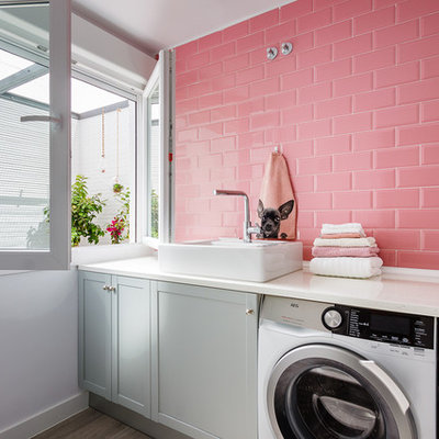 Example of a mid-sized trendy single-wall ceramic tile and gray floor dedicated laundry room design in Madrid with a single-bowl sink, gray cabinets, white walls, a side-by-side washer/dryer and shaker cabinets