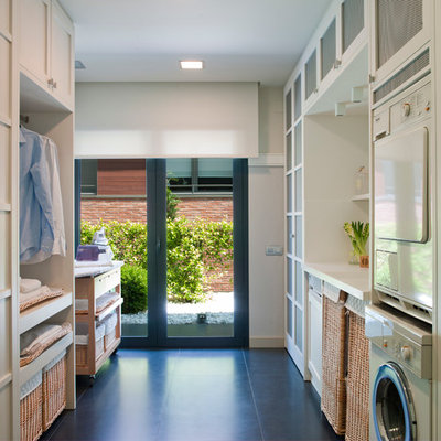 Example of a mid-sized transitional galley ceramic tile dedicated laundry room design in Barcelona with recessed-panel cabinets, white cabinets, solid surface countertops, white walls and a stacked washer/dryer