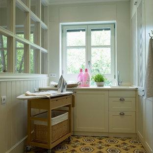 Idee per una lavanderia multiuso country di medie dimensioni con lavello a vasca singola, ante con bugna sagomata e pavimento con piastrelle in ceramica