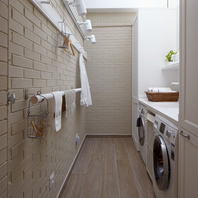 Dedicated laundry room - small industrial galley medium tone wood floor and beige floor dedicated laundry room idea in Barcelona with an integrated sink, recessed-panel cabinets, white cabinets, solid surface countertops, beige walls, a side-by-side washer/dryer and beige countertops
