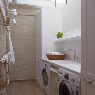 Idéer för att renovera en mellanstor industriell linjär tvättstuga enbart för tvätt, med en enkel diskho, vita väggar, en tvättmaskin och torktumlare bredvid varandra, luckor med infälld panel och vita skåp